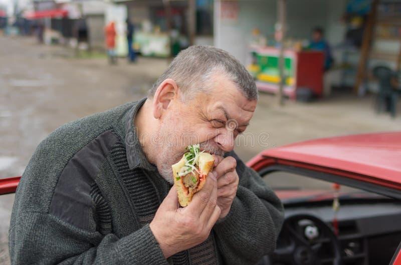 吃在lavash的资深司机lyulya kebab在他的汽车外面 免版税库存照片