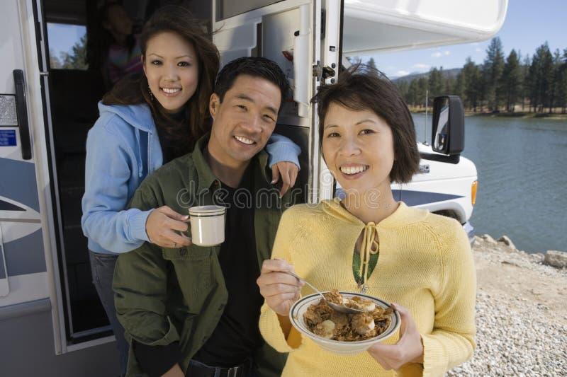 吃在RV的父母和十几岁的女儿早餐在湖 免版税库存图片