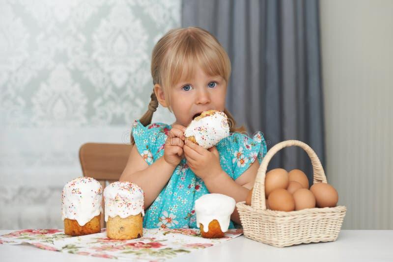 吃复活节蛋糕和鸡蛋的孩子 免版税库存照片