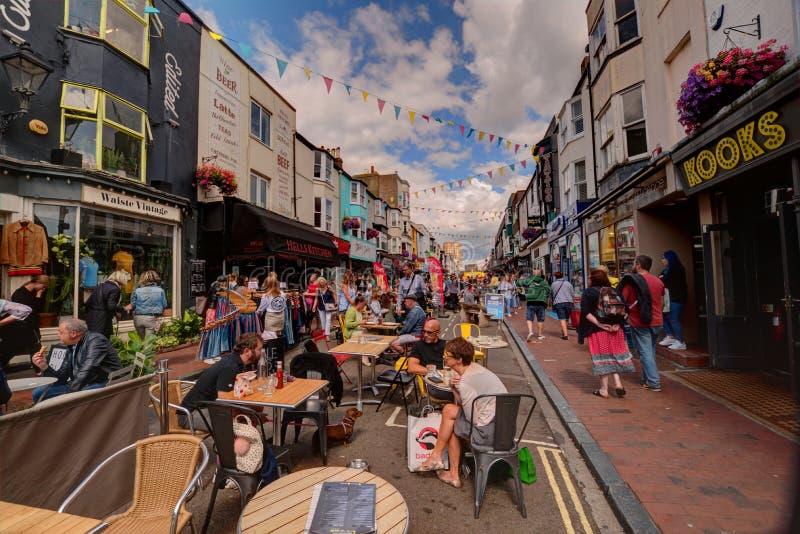 吃外面在街道的人们在布赖顿,英国 免版税库存照片