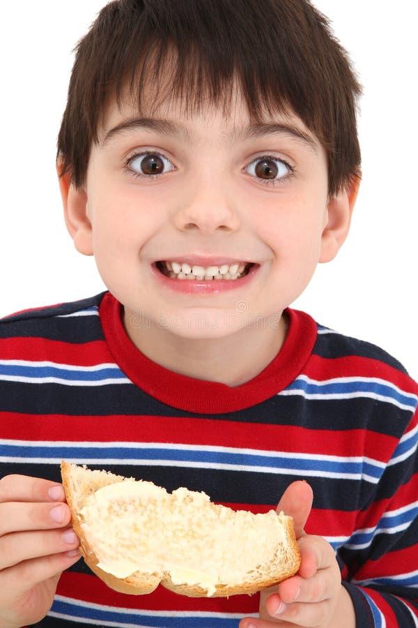 吃多士的男孩黄油 免版税库存照片