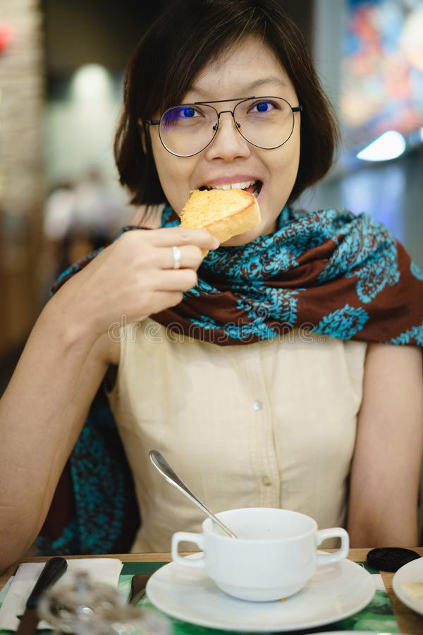 吃多士面包的亚裔妇女 免版税库存照片