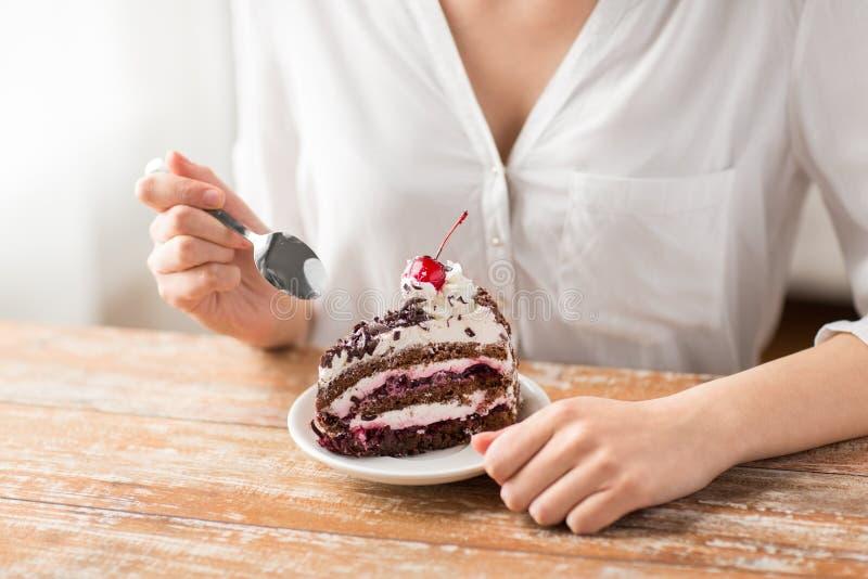 吃夹心蛋糕的片断妇女用樱桃 免版税库存图片