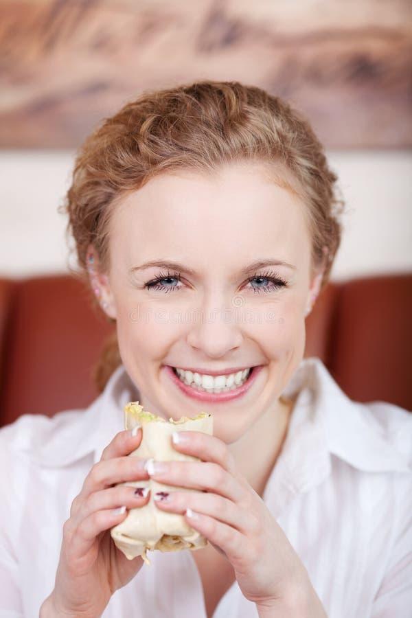 吃套的微笑的白肤金发的妇女 免版税库存照片