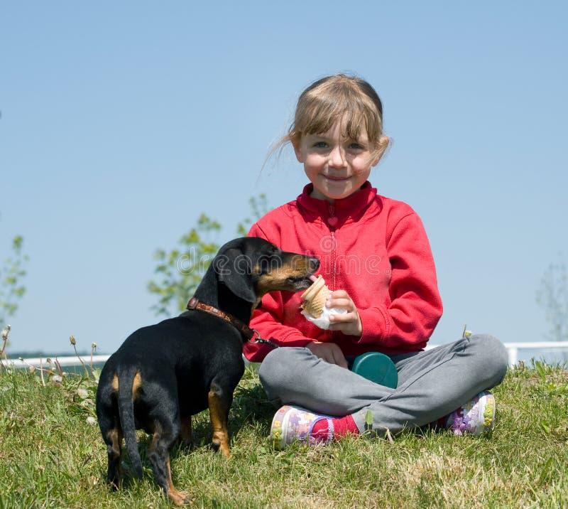 吃女孩冰淇凌的狗 免版税库存图片