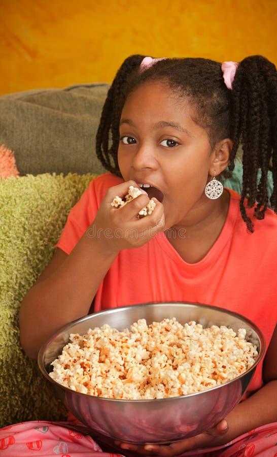 吃女孩少许玉米花 免版税库存照片