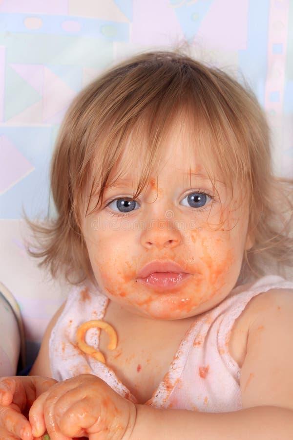 吃女孩杂乱意粉的婴孩 免版税库存图片
