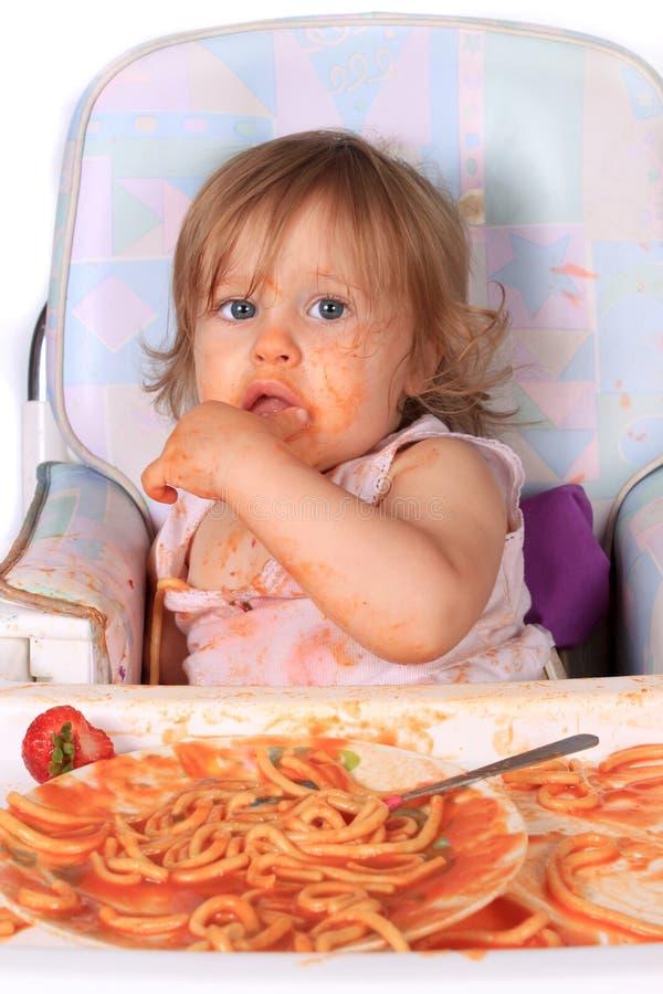 吃女孩杂乱意粉的婴孩 图库摄影