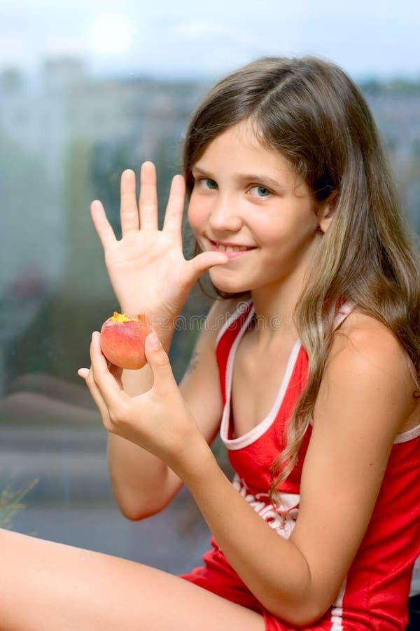 吃女孩桃子微笑 图库摄影