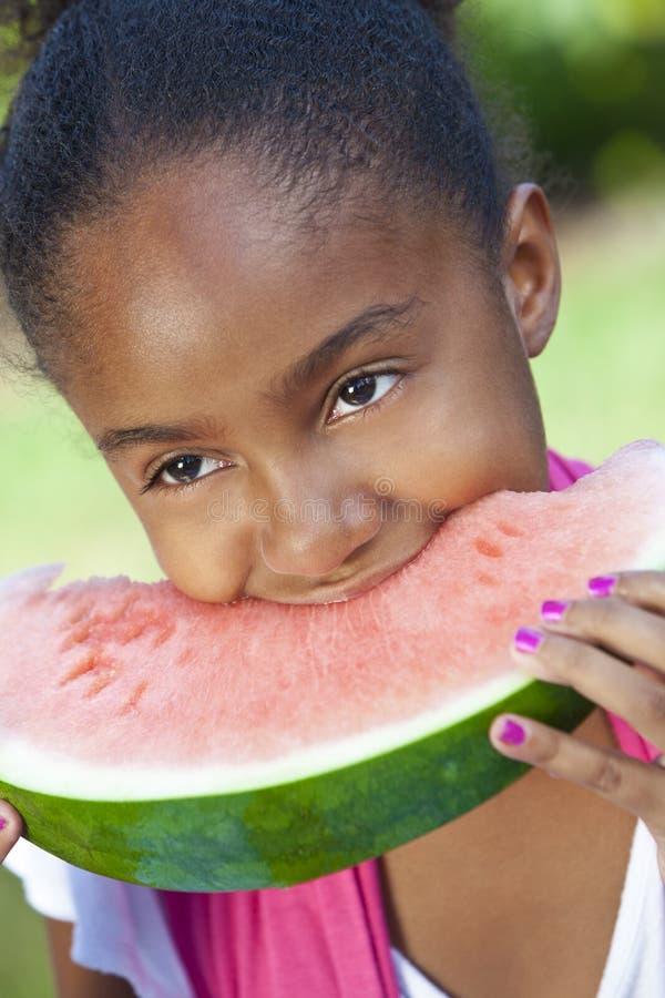 吃女孩瓜水的非洲裔美国人的子项 图库摄影