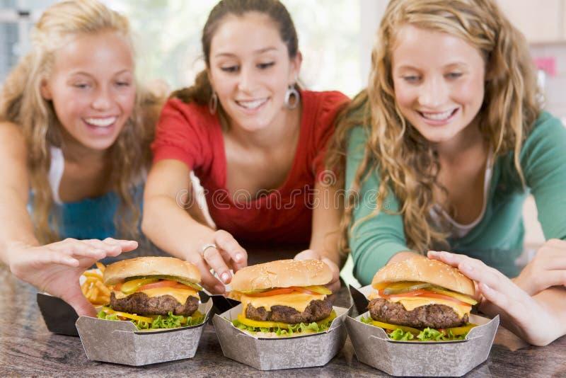 吃女孩的汉堡少年 免版税库存照片