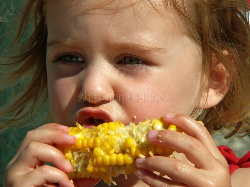 吃女孩的玉米棒玉米 免版税库存照片