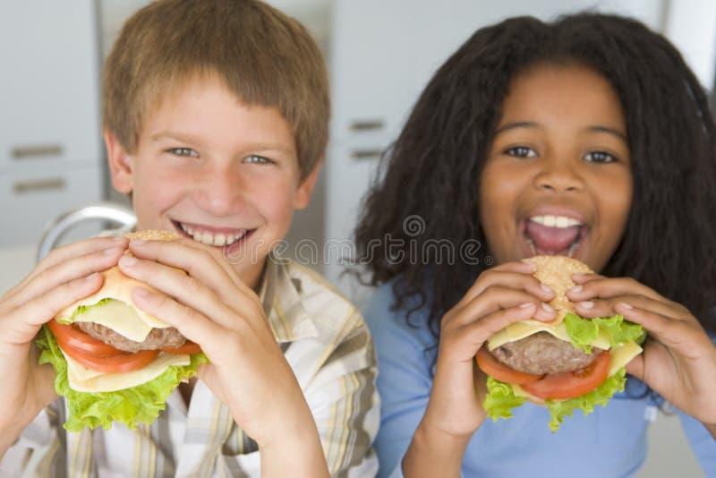 吃女孩的男孩汉堡健康 库存图片