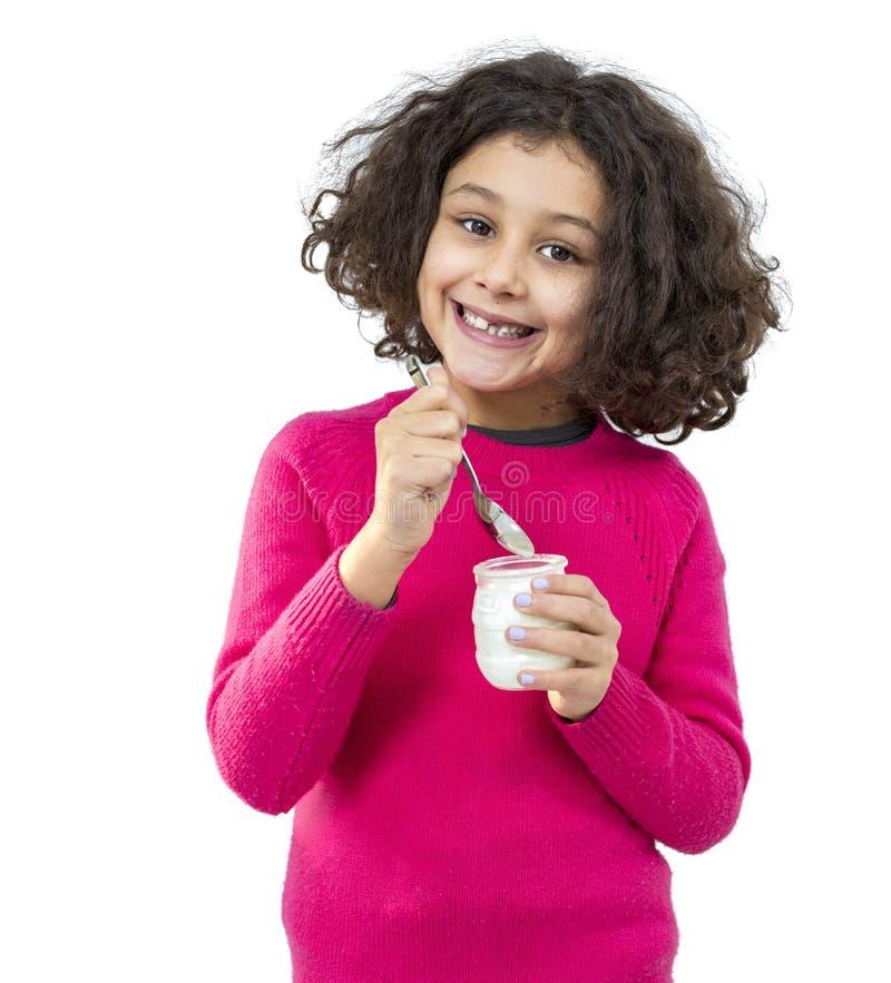 吃女孩的背景查出少许空白酸奶 免版税库存图片