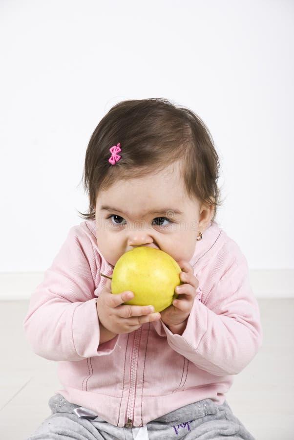 吃女孩的苹果婴孩 免版税图库摄影