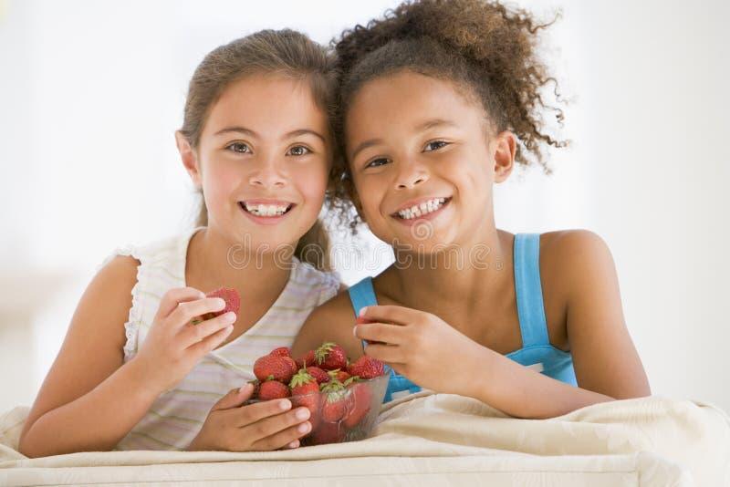吃女孩草莓二个年轻人 免版税库存照片