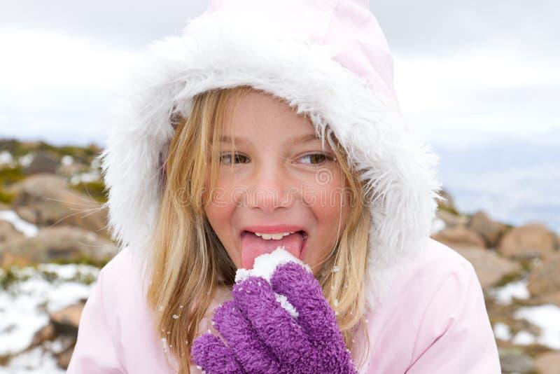 吃女孩雪 免版税库存图片