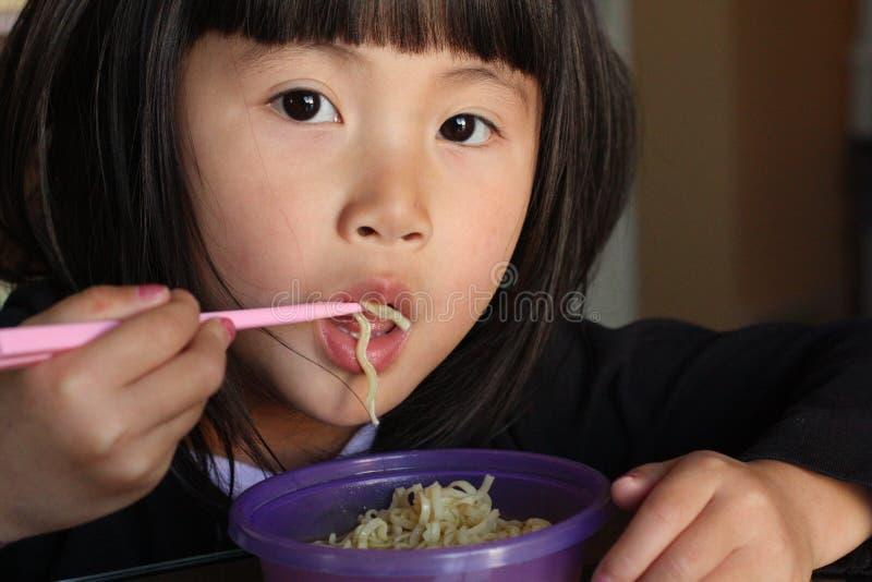 吃女孩面条的亚洲人 库存图片