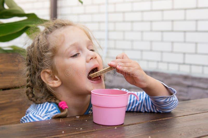 吃奶蛋烘饼和喝茶的四年女孩在游廊的一张桌上 免版税库存图片