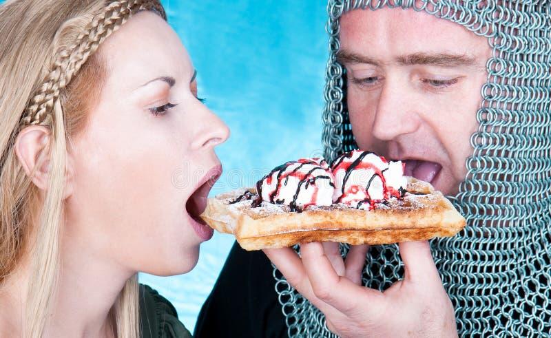 吃奶蛋烘饼用冰淇凌的骑士和王子 免版税库存照片