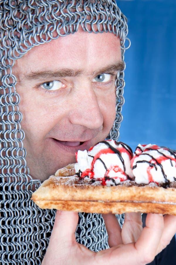 吃奶蛋烘饼用冰淇凌的骑士 库存图片