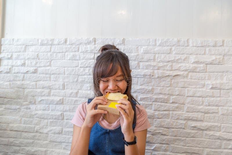 吃奶酪面包格栅的女孩 库存照片