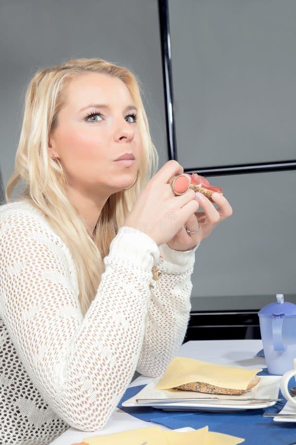 吃她的早餐的体贴的妇女 免版税库存图片