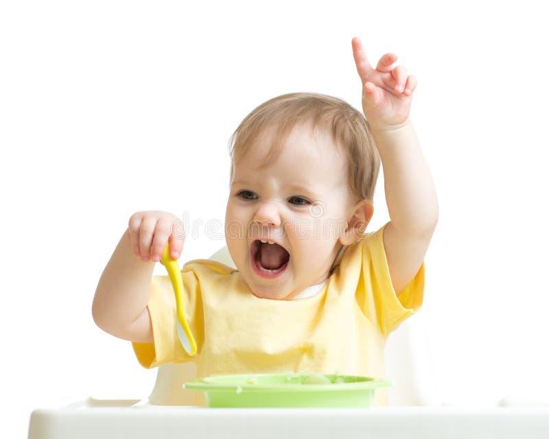 吃她的晚餐的女婴隔绝在白色 免版税库存图片