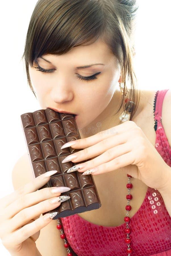 吃妇女年轻人的深色的巧克力 免版税库存图片