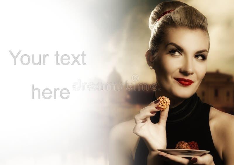 吃妇女年轻人的美丽的巧克力 免版税库存照片