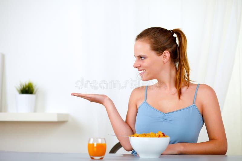 吃妇女年轻人的美丽的白肤金发的早餐 免版税库存图片