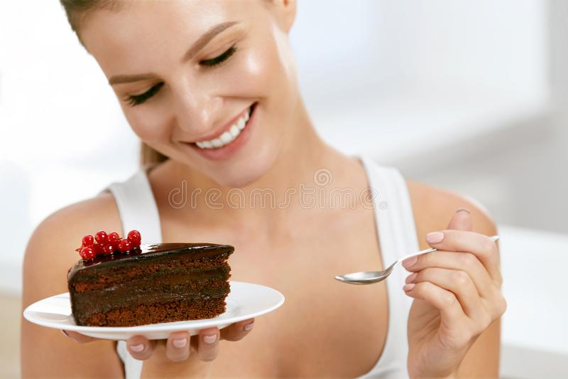 吃妇女的蛋糕 美丽的女性吃点心 免版税库存图片