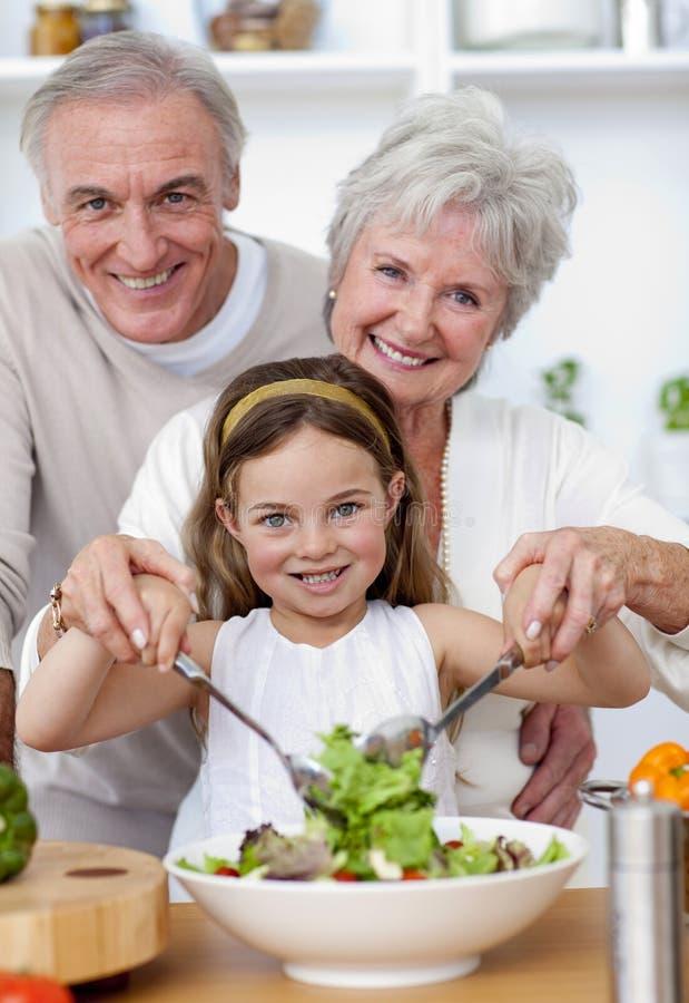 吃孙女祖父项沙拉 免版税图库摄影
