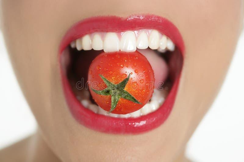 吃宏观嘴红色蕃茄妇女 库存照片