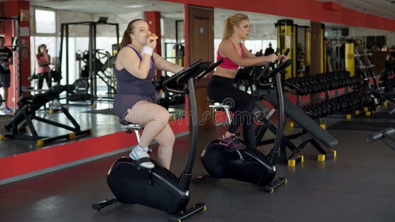 吃小圆面包和骑在健身房,健身的懒惰肥头大耳的妇女固定式自行车 图库摄影