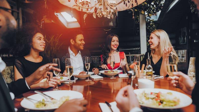吃小组愉快的朋友遇见和晚餐 免版税库存照片