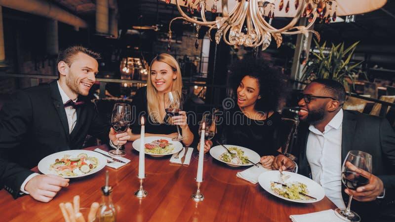 吃小组愉快的朋友遇见和晚餐 库存图片