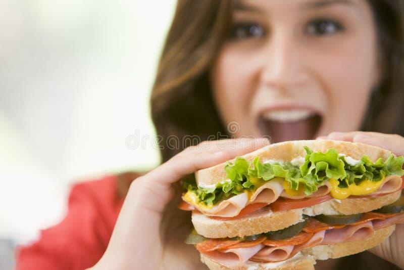 吃少年女孩的三明治 免版税图库摄影
