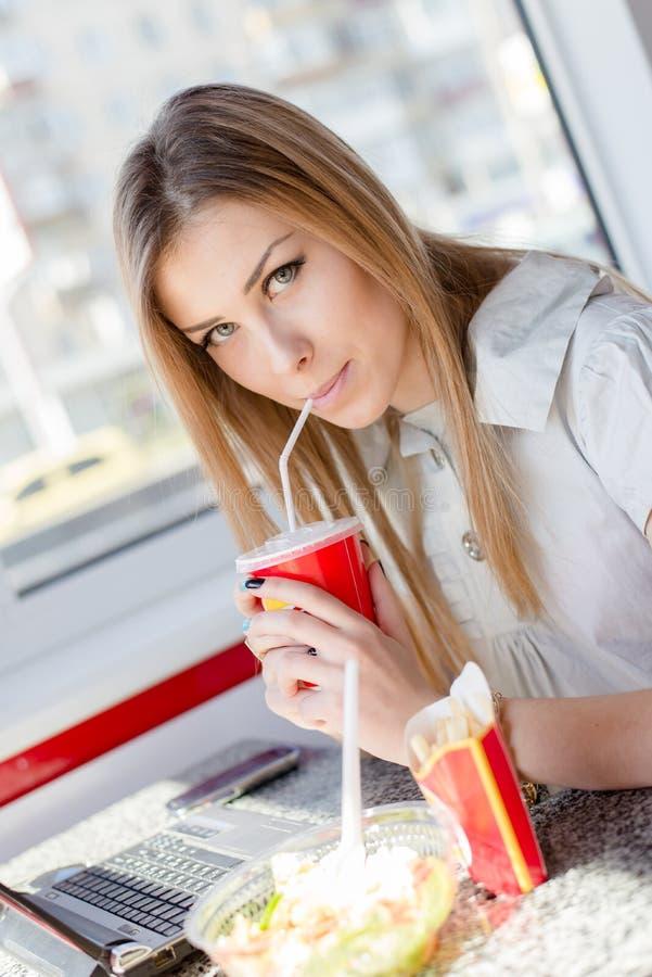 吃工作:关闭喝&吃获得美丽的年轻女商人逗人喜爱的白肤金发的女孩画象研究膝上型计算机的乐趣 库存照片