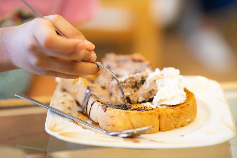 吃巧克力冰淇淋多士面包,选择聚焦的孩子的手 免版税库存照片