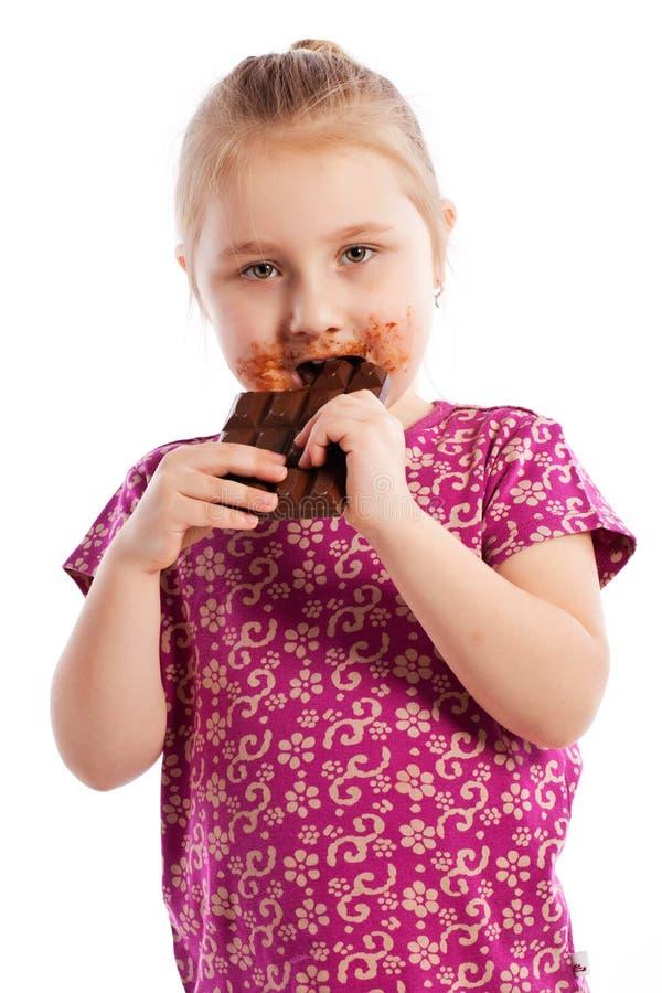 吃巧克力块的女孩。 库存照片