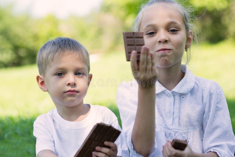 吃巧克力块的男孩和女孩 免版税库存图片