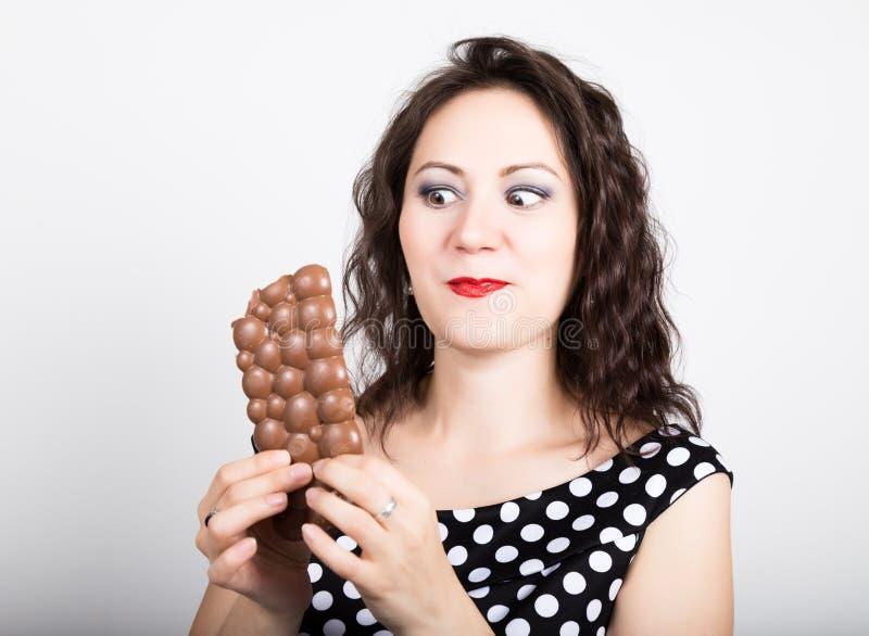 吃巧克力块的美丽的少妇,穿有圆点的一件礼服 库存照片