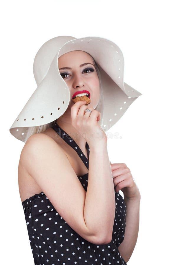 吃巧克力曲奇饼的可爱的妇女 库存照片