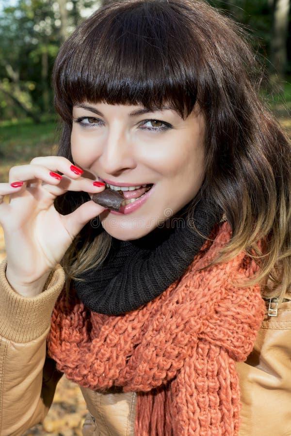 吃巧克力曲奇饼的少妇户外 免版税库存照片