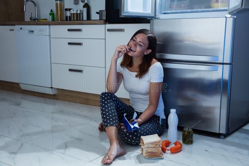 吃巧克力的妇女在厨房里 免版税库存图片