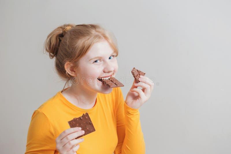 吃巧克力的滑稽的女孩 库存照片
