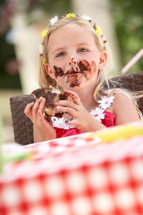 吃巧克力蛋糕的杂乱女孩 免版税库存照片