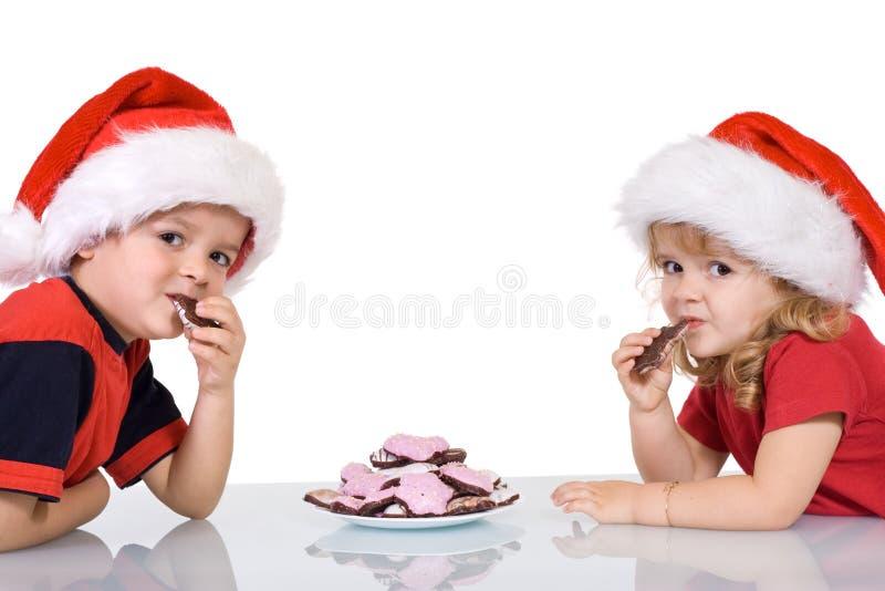 吃帽子孩子圣诞老人的曲奇饼 免版税库存照片