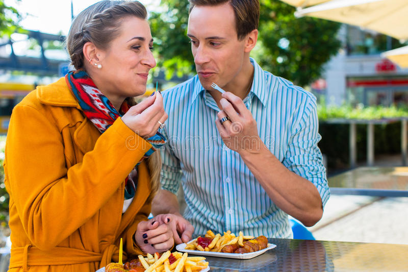 吃德国人Currywurst的夫妇 库存图片